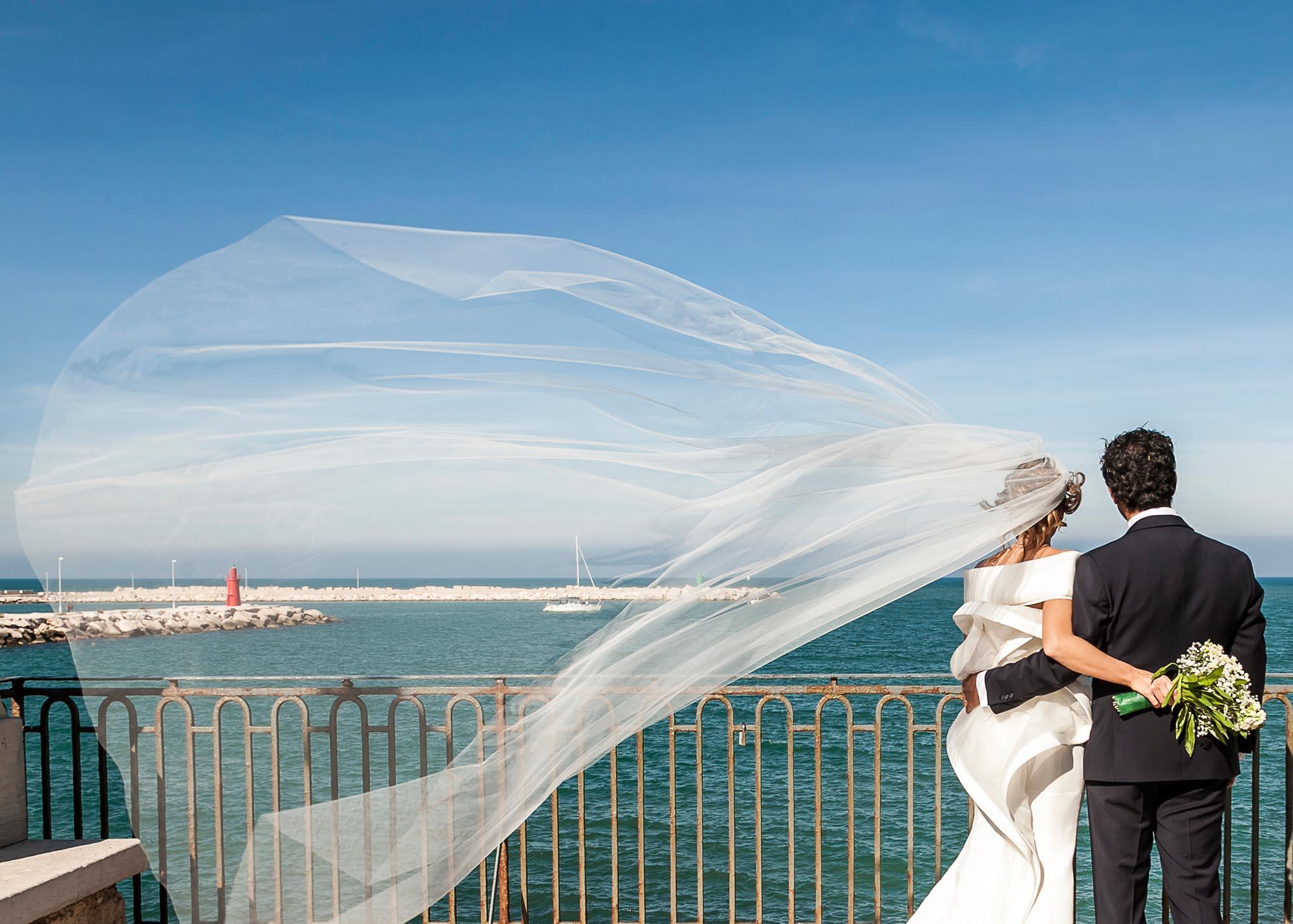 fotografo di matrimonio in puglia sposi al mare con velo al vento